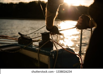 Silhouette of a sailors hands on a winch rope on a sailboat on a sunset. Shot with a selective focus.