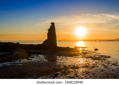 Silhouette of Saint Sadurninho historical tower ruins on the shore at beautiful sunset in Cambados city