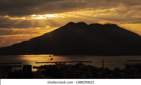 The silhouette of Sakurajima volcano, Kyushu, Japan, with volcanic smoke and gases. The sunrise behind the mountain made beautiful crepuscular ray shines on the ferry and sea of Kagoshima.