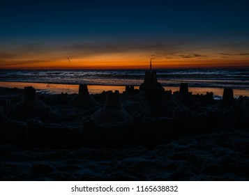 Silhouette of a sand castle on waterline at sunset