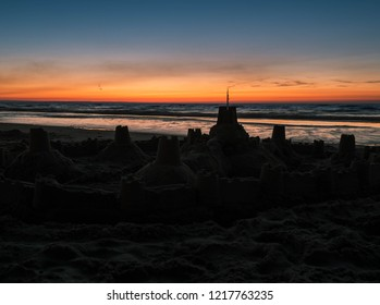 Silhouette of a sand castle on the waterline after sunset