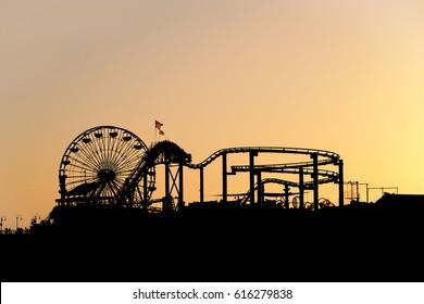 silhouette of santa monica pier amusement park with ferris wheel at sunset as seen form the beach