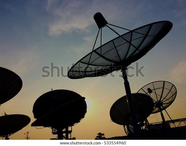 Silhouette of satellite dish at sunset