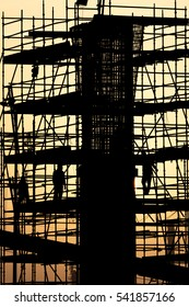 Silhouette of scaffold platform around a pillar in a construction site - early morning sunrise