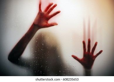 silhouette  scared girl hand with red blood behind glass door , horror background