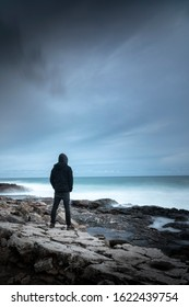 Silhouette scene of a hooded man who looks like a fighter, dressed in black in a cove, looking at the maritime horizon. Inspirational and emotional aesthetics.