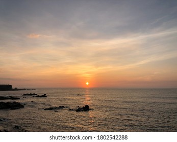 Silhouette scenic view of dramatic sunrise sky against Pacific Ocean at inubosaki, Choshi Japan. Partially cloudy. Hazy sky view. Moment of natural climate scenery.