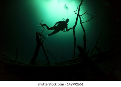 Silhouette of a scuba diver in blue / green water in a fresh water cenote / cavern / cave - Cenote Angelita, Riviera Maya, Mexico