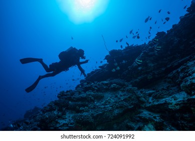 Silhouette of a scuba diver diving with a rebreather on a deep Hawaiian tropical rocky reef in clear blue water.