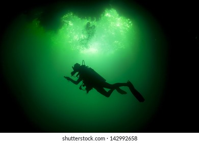 Silhouette of a scuba diver in green water in a fresh water cenote / cavern / cave - Cenote Angelita, Riviera Maya, Mexico