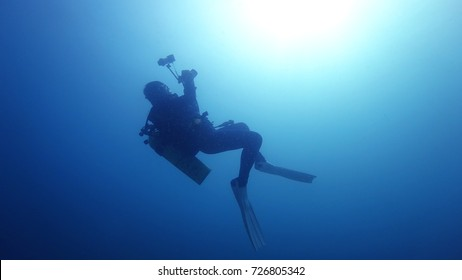 silhouette of scuba diver taking photos