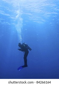 Silhouette of a scuba diver in the water in a upright position breathing air