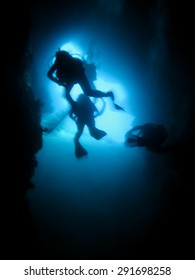 Silhouette of scuba divers in an underwater cave. Cave diving