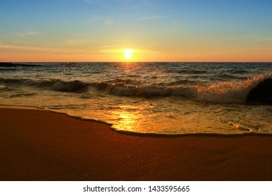Silhouette sea waves on the beach over sunset sky, peaceful and calm atmosphere.