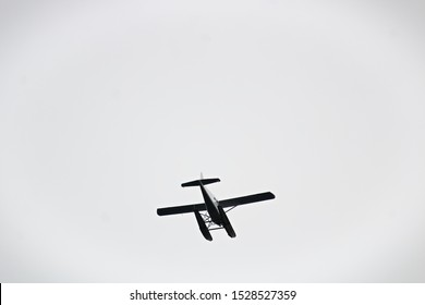 Silhouette of a seaplane underside against a gray background
