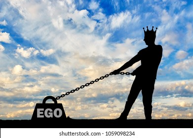 The silhouette of a selfish man with a crown on his head draws a heavy load under the name of the ego. The concept of selfishness and narcissism as a problem for a normal life