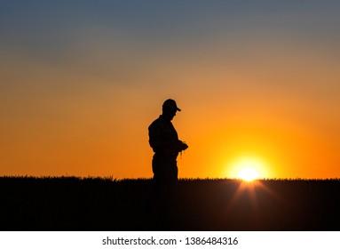 Silhouette of senior farmer walking in field examining crop at sunset.