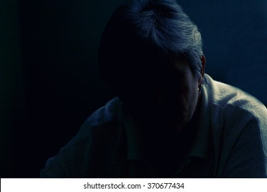 Silhouette of an senior lady sitting in a dark space with a little of light on her hair and shoulder