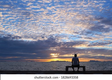 Silhouette of senior man sitting alone on the bench in front of the sea in the evening, Man sitting  on the bench and watching sunset over the sea at Samui Thailand