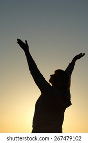 The silhouette of a senior woman reaching up to the sky, awaiting a better future and thankful for the day. Hope/gratitude/health concept.