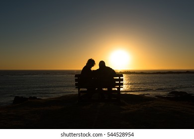 Silhouette of a seniors couple enjoying a colorful sunset on the bench at the ocean