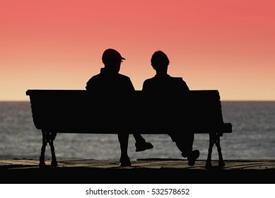 Silhouette seniors couple waiting for colourful sunset on the bench near ocean