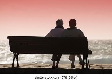 Silhouette seniors couple waiting for colourfull sunset on the bench near ocean