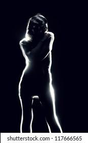 silhouette of sensual girl in light rays at dark