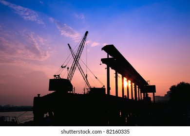 Silhouette of several cranes working at sunset in a harbor