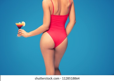 Silhouette of sexy fit woman in red swimsuit holding colorful drink in hand, posing on blue background.
