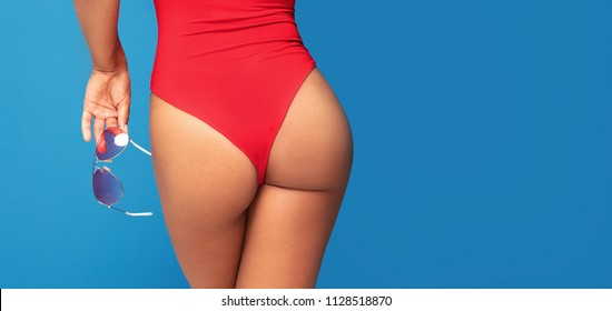 Silhouette of sexy fit woman in red swimsuit holding fashionable sunglasses in hand, posing on blue background.