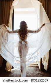 Silhouette of sexy young brunette woman in white lingerie underwear boudoir dress in the doorway opening curtains