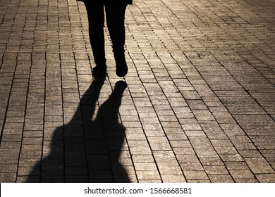 Silhouette and shadow of fat woman walking on a dark street, rear view. Concept of loneliness, overweight, human life