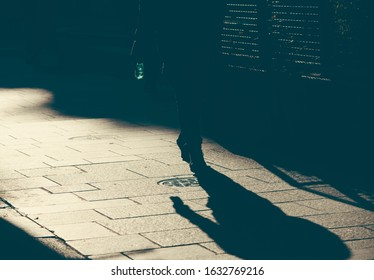 Silhouette and shadow of lonely human walking on a street. the legs on a sidewalk. Concept of loneliness and dramatic story in human life.