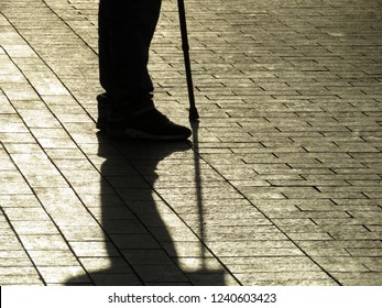 Silhouette and shadow of man standing with a cane. Concept of blind person, disability, old age, diseases of the spine, stranger