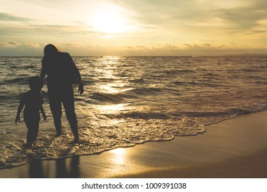 Silhouette shadow of mother and son playing on golden sunset beach