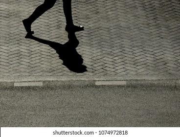 Silhouette shadow of people walking on street floor