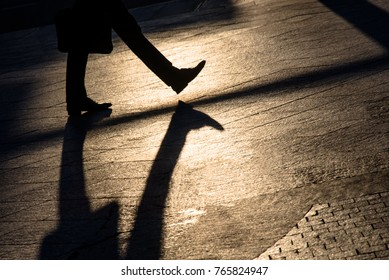 Silhouette and shadow of a people walking on a city sidewalk