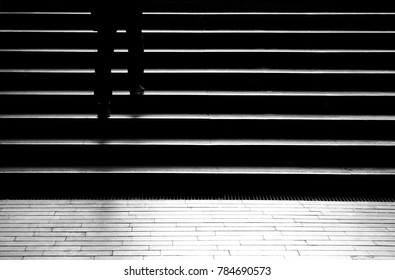 Silhouette shadow of person legs walking up the public stairs in subway passage on the night in black and white