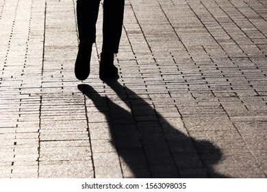 Silhouette and shadow of person walking on a street. Concept of loneliness, dramatic story, human life