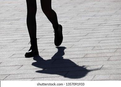 Silhouette and shadow of slim girl walking on the street. Female legs on a sidewalk, concept of workout, running woman, slimming in spring season