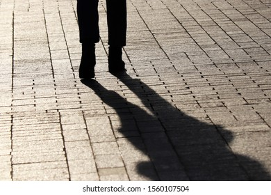 Silhouette and shadow of slim girl walking down on a street, rear view. Concept of loneliness, dramatic stories, human life