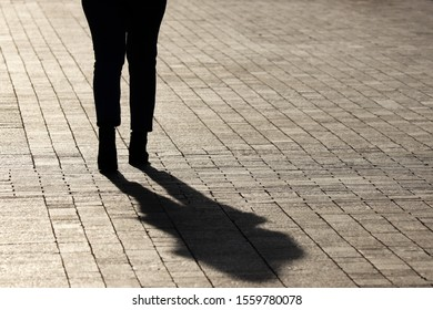Silhouette and shadow of woman walking down on a street, rear view. Concept of loneliness, parting, dramatic stories, human life