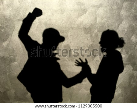 Silhouette shadows on a wall of aggressive man hitting innocent woman in the street.