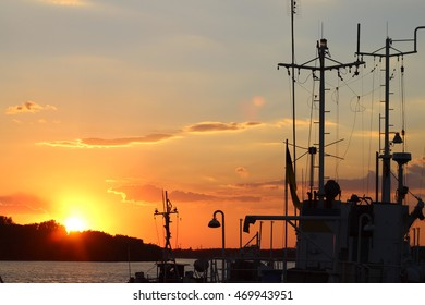 Silhouette of the ship near the pier in the river Danube at sunset