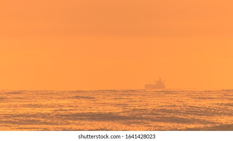 A silhouette of a ship in a shipping channel during an intense summer's sunrise on the Sunshine Coast in Queensland, Australia.