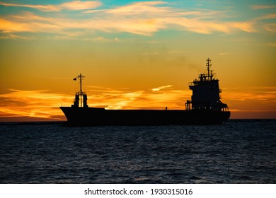 a silhouette of a ship at sunset.
