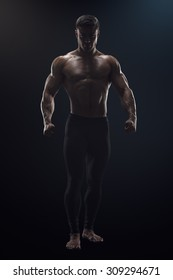 Silhouette of a shirtless strong bodybuilder preparing for training. Dramatic concept photo of confident young fitness man with core muscles, power hands and clenched fists.