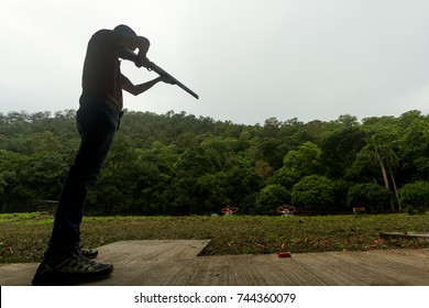 Silhouette of Shooter is Playing Skeet Shooting Sport by Shot Gun. Copy Space for Text.