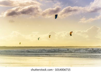 Silhouette shot of kite surfers Atlantic Ocean with puffy clouds and early morning sun